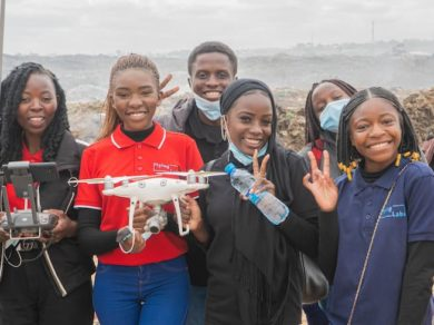 Students smiling holding a drone