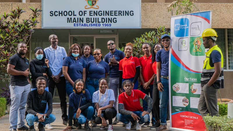 Zambia Flying Labs and training participants standing in front of the School of Engineering Main Building